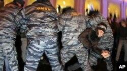 一名抗議者星期一在聖彼得堡掙扎逃脫警察的捉捕