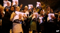 In this photo released by the Iranian Students News Agency, ISNA, Iranians hold posters of President Hassan Rouhani as they welcome Iranian nuclear negotiators upon their arrival from Geneva at the Mehrabad airport in Tehran, Nov. 24, 2013.