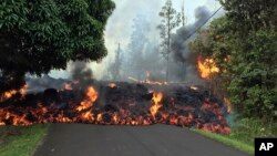 Photo provided by the U.S. Geological Survey shows a lava flow moving across Makamae Street in the Leilani Estates subdivision near Pahoa on the island of Hawaii, May 6, 2018.