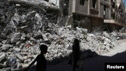Anak-anak berjalan di antara puing-puing bangunan di Ain Tarma, distrik Ghouta, pinggiran Damaskus yang dikuasai pemberontak (foto: dok). Pasukan pro pemerintah meningkatkan serangan terhadap Ghouta timur.