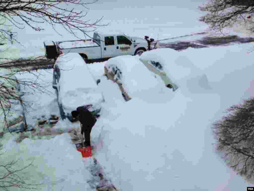 为了可以准时上班,VOA员工雪一停就开始清理门前的积雪。