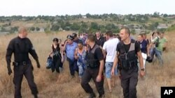FILE - Ukrainian police officers escort the Roma residents from the village of Loshchynivka, Odessa region, Ukraine, in this image made from video taken Aug. 28, 2016. Ukrainian police evacuated a group of Roma residents from a southern town after villagers ransacked their homes.