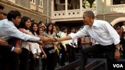 Durante su presentación para promover las exportaciones estadounidenses, el presidente Obama saluda a estudiantes universitarios en India.