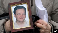FILE - A portrait of lawyer Sergei Magnitsky, who died in jail.