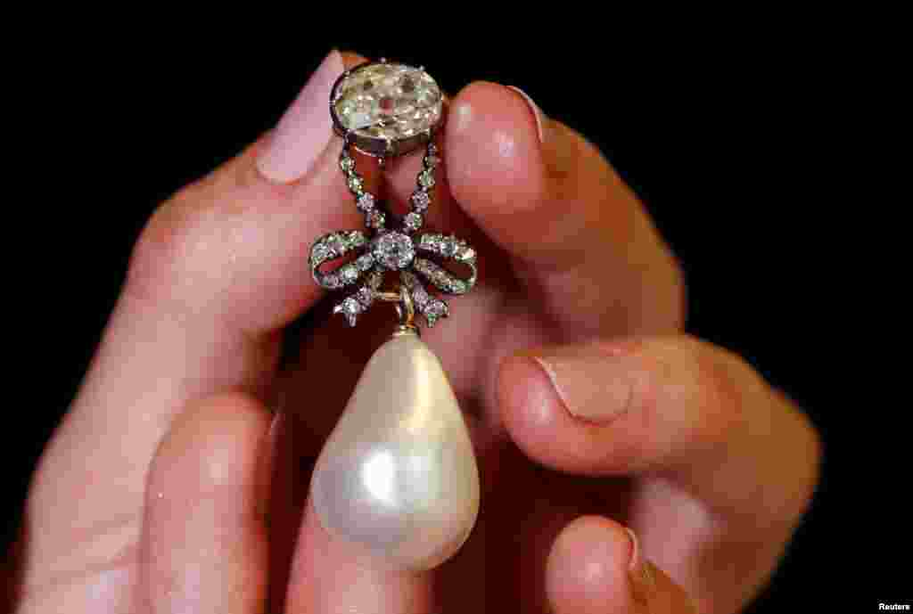 "A natural pearl and diamond pendant once owned by Marie Antoinette is held by a model during a press preview ahead of the upcoming auction ""Royal jewels from the Bourbon Parma Family"" at Sotheby's in Geneva, Switzerland."