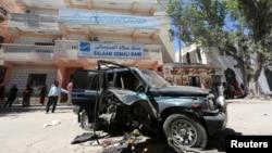 Warga mengamati sisa-sisa mobil milik anggota parlemen Somalia Isaak Mohamed Rinoco, yang tewas akibat bom yang dipasang di mobilnya oleh militan Islam di distrik Hamaerweyne, Mogadishu (21/4). Al-Shabab mengaku bertanggung jawab atas tewasnya seorang lagi anggota parlemen Abdiaziz Isaq Mursal, Selasa (22/4) di Madina, Mogadishu.