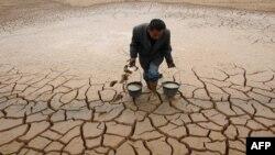 Một nông dân lấy nước từ 1 ao khô cạn để tưới cây ở tỉnh Giang Tây, Trung Quốc