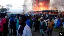 Warga Papua berkumpul di dekat toko yang terbakar dalam aksi protes di Wamena, provinsi Papua, 23 September 2019.