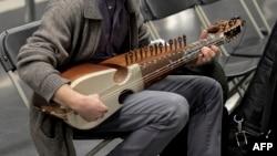 FILE - A musician checks his sarangi in a Barcelona subway station, Nov. 27, 2015.
