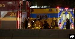 Firefighters stage near the area where a suspect in a series of bombing attacks in Austin blew himself up as authorities closed in, early March 21, 2018, in Round Rock, Texas.
