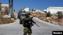 Seorang tentara Israel memberi aba-aba dalan operasi penggeledahan pasca insiden penikaman di dekat Beit Fajjar, permukiman Yahudi di Tepi Barat yang diduduki Israel, 8 Agustus 2019.