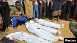 FILE - A man sits as others stand near the wrapped up bodies of children from the same family, one day after they were killed in a Saudi-led airstrike on their house in Bajil district of the Red Sea province of Houdieda, Yemen, Oct. 8, 2016.