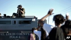 Pripadnik policije Sentt Luisa upire oružje u grupu demonstranata u Fergusonu, 13. avgusta 2014.