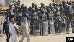 Para petani berjalan melewati pasukan keamanan yang berjaga di perbatasan Singu di New Delhi, 27 Januari 2021, saat polisi menutup beberapa jalan utama sehari pasca serbuan petani di ibu kota. (Foto: Money SHARMA / AFP)