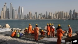 FILE - Laborers work at a construction site at the Palm Jumeirah, in Dubai, United Arab Emirates.