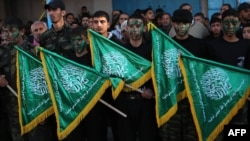 FILE - Palestinian youths hold Hamas movement flags during a rally near the Rafah border between southern Gaza Strip and Egypt on February 5, 2015.