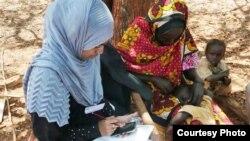 کینیا کے ایک دیہی علاقے میں ریڈ کراس کی رضاکار سروے کے لیے موبائل فون استعمال کر رہی ہے۔