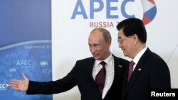 Russia's President Vladimir Putin (L) greets China's President Hu Jintao upon his arrival at the APEC Summit in Vladivostok, September 8, 2012.