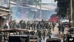 Des policiers kenyans pourchassent des manifestants qui ont érigé une barricade en flammes sur une rue, dans le bidonville de Kibera, à Nairobi, 23 mai 2016.