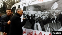 A man cries next to a poster with an image of Chokri Belaid, a prominent Tunisian opposition politician who was shot dead, Tunis February 7, 2013.