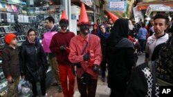 """Iranian youths, wearing red clothes and black makeup as a symbol of the Iranian New Year, sing and play tambourine at Tajrish square in northern Tehran, Iran, ahead of the Iranian New Year, or Nowruz, meaning """"new day,"""" March 18, 2017."""
