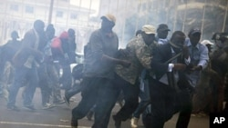 Anti-government protestors run from tear gas in Senegal's capital Dakar, February 15, 2012