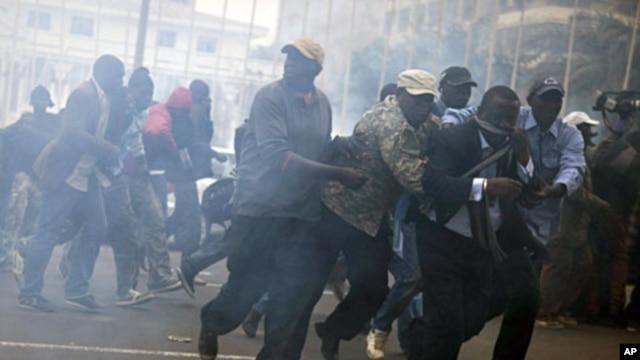 Anti-government protestors run from tear gas in Senegal's capital Dakar, February 15, 2012