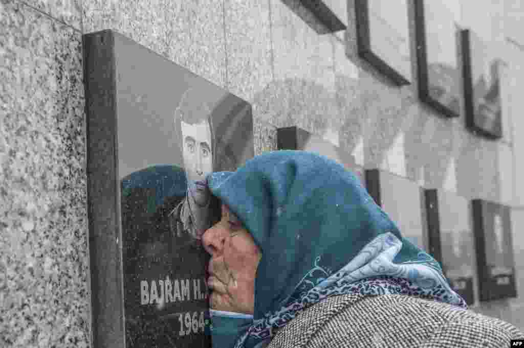 A Kosovo Albanian woman Vezire Gjeladini, 76, kisses the picture of her son etched into a commemorative plaque and placed on a wall dedicated to the victims of the Racak massacre, Kosovo. In 1999, forty-five Albanian civilians were killed by Serb forces, in the village of Racak.