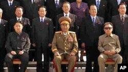 លោក Kim Jong Un  (រូបឆ្វេង) អាយុជាង២០ឆ្នាំ អង្គុយនៅពីរកៅអីឃ្លាតពីលោក Kim Jong Il (រូបស្តាំ) ដោយពាក់អាវធំស្រដៀងគ្នានឹងអាវធំពណ៌កាគីរបស់ឳពុកលោក។