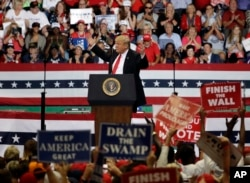 FILE - President Donald Trump reacts as supporters wave signs during a rally, Oct. 31, 2018, in Estero, Florida.