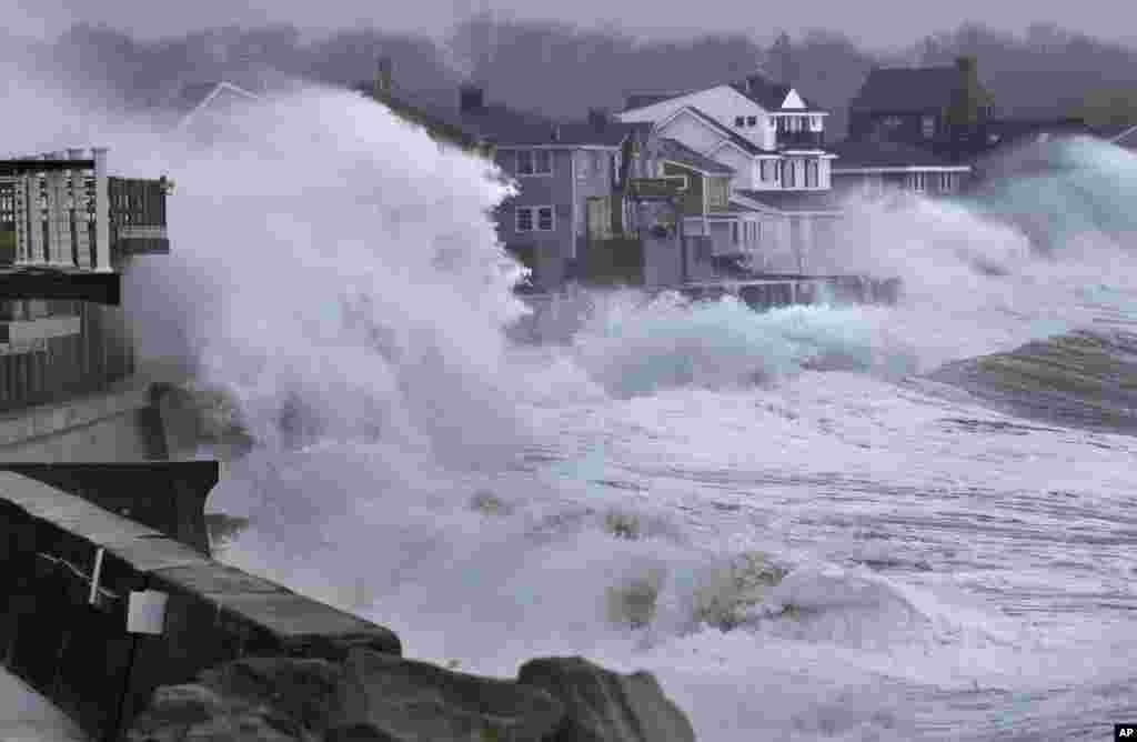 Gelombang laut menabrak dinding pembatas pantai dan masuk ke rumah-rumah di sepanjang pantai Scituate, Massachusetts, AS.