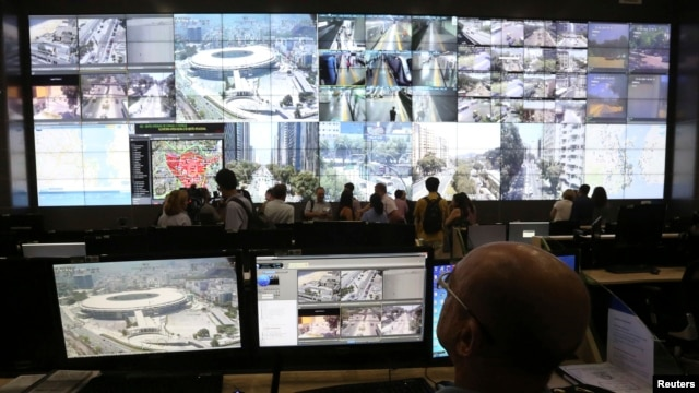 FILE- A policeman observes a screen displaying the Maracana stadium during a media tour at the security center for the 2014 soccer World Cup in Rio de Janeiro, Jan. 22, 2014.
