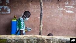 Nhân viên y tế phun thuốc khử trùng xung quanh khu vực người đàn ông (phải) bị nghi nhiễm virust Ebola, trước khi đưa người này lên xe cứu thương ở Freetown, Sierra Leone, ngày 24/9/2014.