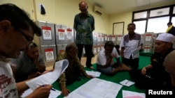 Election commission official Dedi Saidi, left, reads a document stating the number of votes collected in ballot boxes, at Bendungan Hilir, Jakarta, Indonesia, July 10, 2014.
