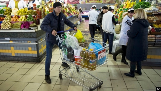 FILE - A man pushes a cart with food items at a grocery store in Moscow, April 2, 2015.