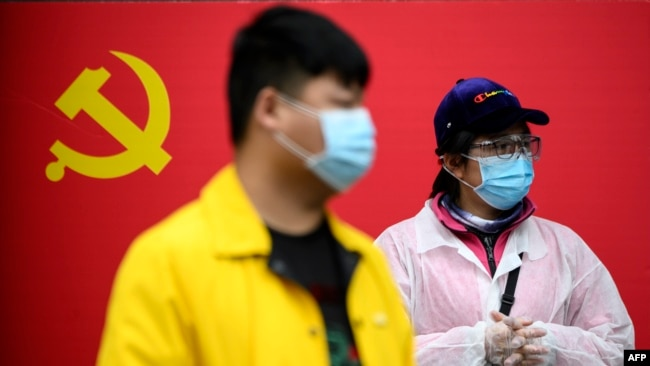 People wearing face masks stand in front of a Communist Party of China flag