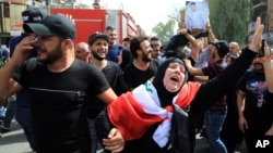 Iraqis grieve during the funeral procession of bomb victim, Akram Hadi, 24, who was killed in a massive truck bomb attack in the Karada neighborhood of Baghdad, Iraq, July 5, 2016.