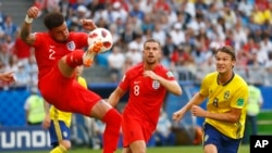 England's Kyle Walker, left, kicks the ball front of England's Jordan Henderson, center, and Sweden's Albin Ekdal, right, at the 2018 soccer World Cup in Samara, Russia. (AP Photo/Matthias Schrader )