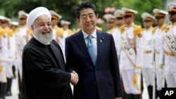 Japanese Prime Minister Shinzo Abe, center, shakes hands with Iranian President Hassan Rouhani during the official arrival ceremony, at the Saadabad Palace in Tehran, Iran, June 12, 2019.