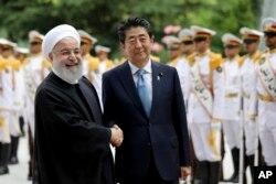 베 신조 일본 총리(오른쪽)와 하산 로하니 이란 대통령이 12일 이란 테헤란 사다바드궁에서 열린 공식 환영식에서 악수하고 있다.