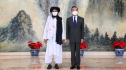 FILE - In this July 28, 2021, photo released by China's Xinhua News Agency, Taliban co-founder Mullah Abdul Ghani Baradar, left, and Chinese Foreign Minister Wang Yi pose for a photo during their meeting in Tianjin, China.