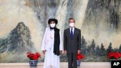 Arhiva - Koosnivač Talibana Mula Abdul Gani Baradar (levo) i ministar inostranih poslova Kine Van Ji poziraju za zajedničku fotografiju tokom sastanka u Tianjinu, Kina, 28. jula 2021. (Li Ran, agencija Sinhua via AP)