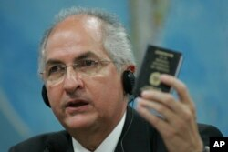 FILE - Caracas' Mayor Antonio Ledezma holds up a small copy of Venezuela's constitution as he addresses the Commission of External Relationships in Brazil's Senate in Brasilia, Oct. 27, 2009.
