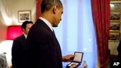 奥巴马总统端详诺贝尔和平奖章