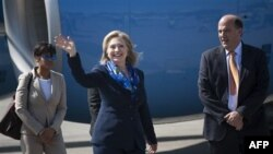Ngoại trưởng Clinton (giữa) vẫy chào các nhà báo tại sân bay ở Haiti