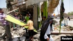 Cư dân kiểm tra hiện trường một vụ đánh bom xe tại khu phố al-Ameen ở Baghdad, Iraq.