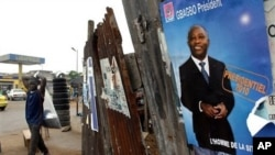 A man walks past an election poster for incumbent President Laurent Gbagbo, as presidential campaigning kicked off Friday, Oct. 15, 2010 in Abidjan, Ivory Coast. Ivory Coast has endured eight years of civil war, and a date for elections has been set and m