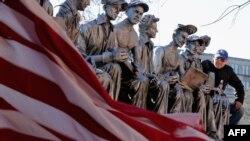 """Seniman Sergio Furnari berpose di sebelah patung buatannya """"Makan Siang di Atas Gedung Pencakar Langit – Penghormatan Kepada Pahlawan Amerika,"""" di luar Serikat Pekerja Industri Besi di Washington DC, 20 November 2015."""