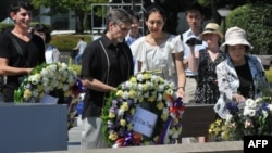 Clifton Truman Daniel (C) offers a wreath of flowers at the memorial cenotaph for the people killed by the atomic bomb at the Peace Memorial Park in Hiroshima, Japan, August 4, 2012.