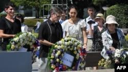 Ông Clifton Truman Daniel (giữa), cháu nội cựu TT Hoa Kỳ Harry Truman, người đã ra lệnh đánh bom nguyên tử Nhật Bản trong Thế chiến thứ II, đặt vòng hoa tại Ðài tưởng niệm Hòa bình ở Hiroshima (4/8/2012)